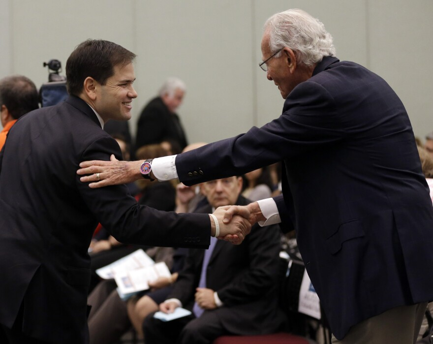 Sen. Marco Rubio (left) shakes hands with automobile magnate Norman Braman following a speech at Miami-Dade College in 2014.