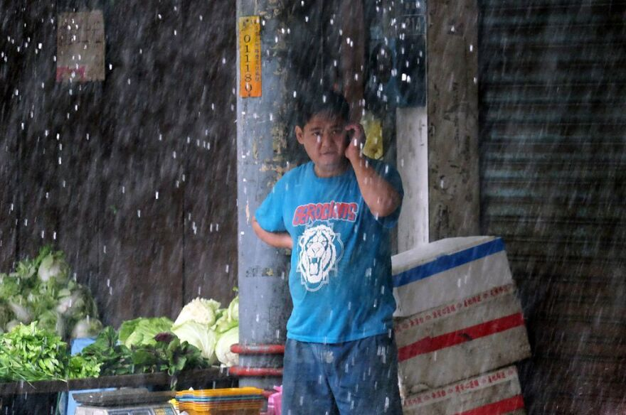A vegetable vendor speaks on the cellphone at a market in Xindian district of New Taipei City, as Typhoon Megi approached Taiwan on Tuesday.