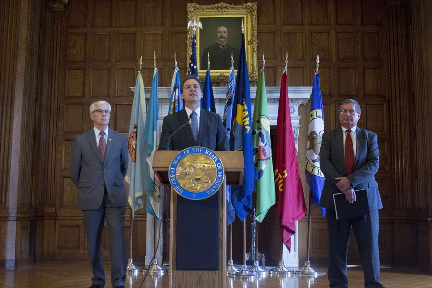 In this archive photo, Governor Steve Bullock stands at a podium with an array of state and tribal nation flags behind him. Lt. Governor Mike Cooney stands at his right hand and Montana Budget Director Tom Livers stands to his left. All men are wearing suits.