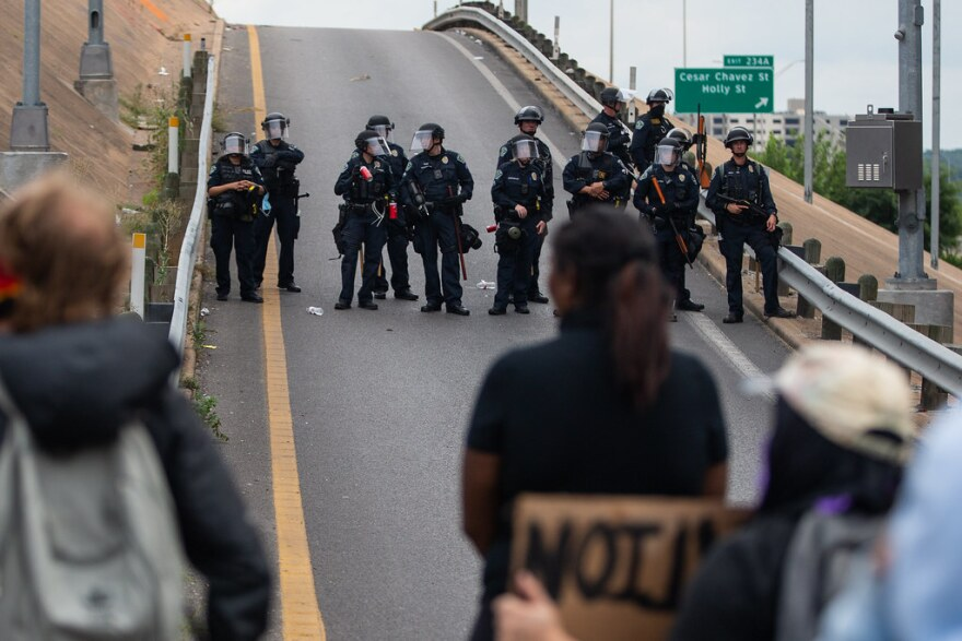 Austin police officers block protesters from getting onto the highway during demonstrations against police violence Sunday.