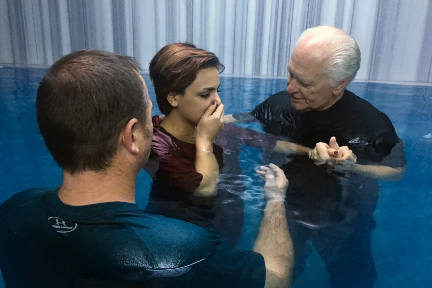 Pastors Karl Vickery and Rick Robinson baptize Iranian refugee Sabah Allahvardi, 22, in a Turkish bathhouse in Denizli.