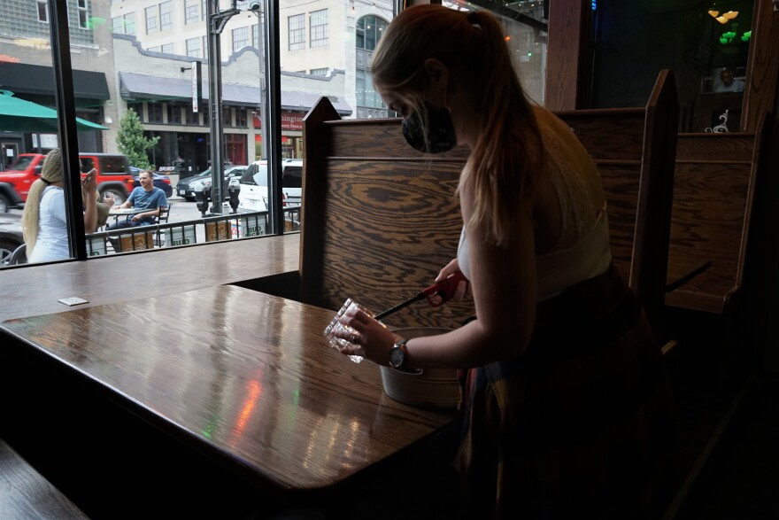 Flannery's Pub manager Jordan Viponel-Gilbert wears a mask as she lights candles at the Washington Avenue watering hole on June 19, 2020.