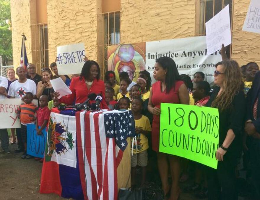 A woman at a podium is surrounded by advocates holding TPS support signs and American flags.