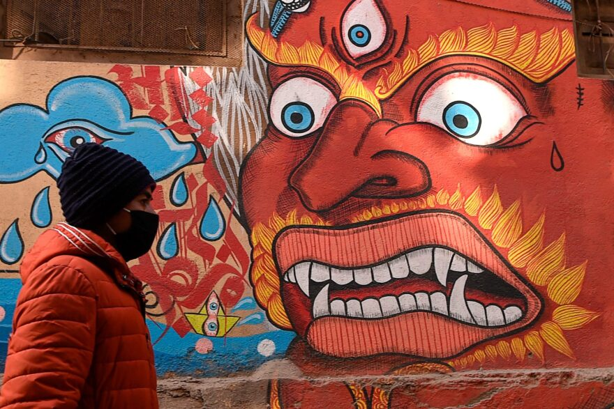A resident wearing a protective facemask walks at the Patan Durbar Square area in Kathmandu.