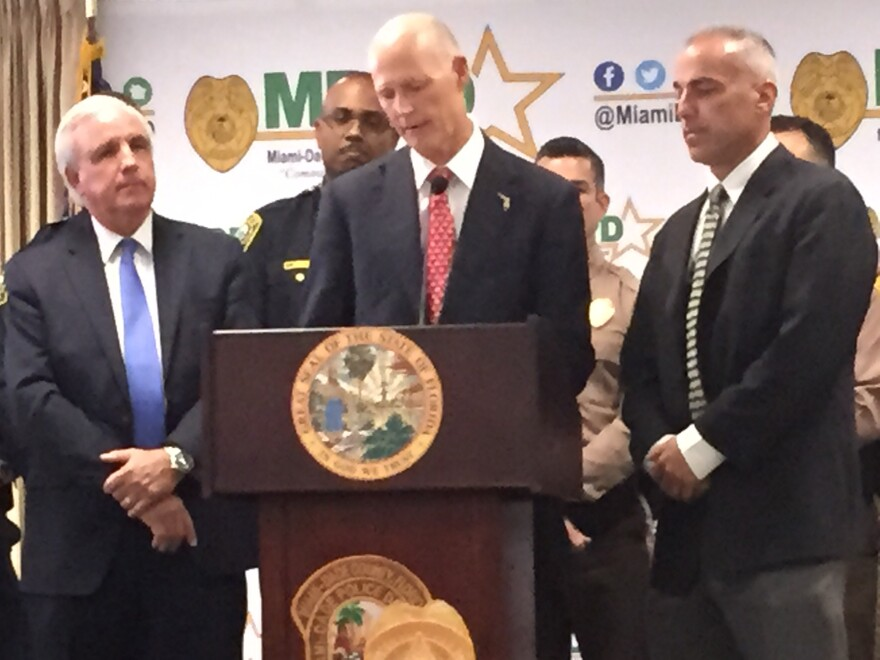 Gov Rick Scott (center) presented his plan flanked by Miami-Dade Mayor Carlos Gimenez (left) and Andy Pollack (right), whose daughter Meadow was killed at the mass shooting at Marjory Stoneman Douglas High.