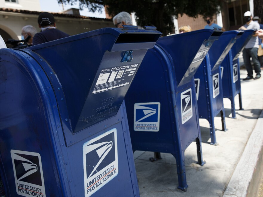 A customer deposits mail into a U.S. Postal Service mail collection box this week in Burbank, Calif.