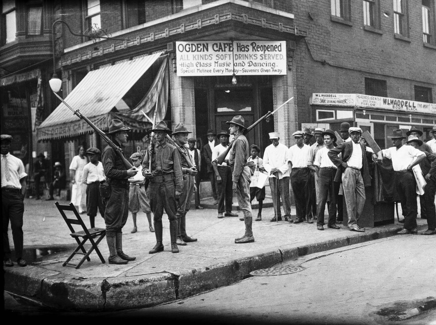 A group of men and armed National Guard in front of the Ogden Cafe during the race riots in Chicago, Illinois, 1919.