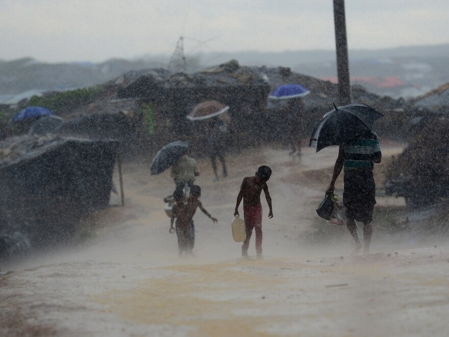 A Rohingya child carries water through a rainstorm at a refugee camp in October 2017.