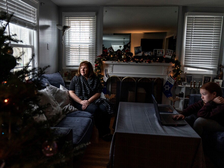Eileen Carroll, left, sits for a portrait as her daughter, Lily, 11, attends school remotely from their home in Warwick, R.I. on Dec. 16. When Carroll's other daughter tested positive for the coronavirus, state health officials told her to notify anyone her daughter might have been around. Contact tracers, she was told, were simply too overwhelmed to do it.