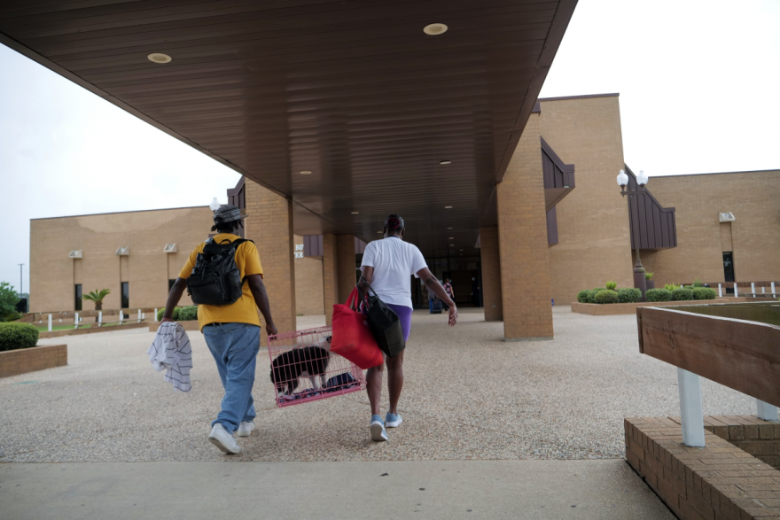 """Evacuees outside the Robert A. """"Bob"""" Bowers Civic Center in Port Arthur, where buses prepared to transport evacuees ahead of Hurricane Laura's landfall on Aug. 26, 2020."""