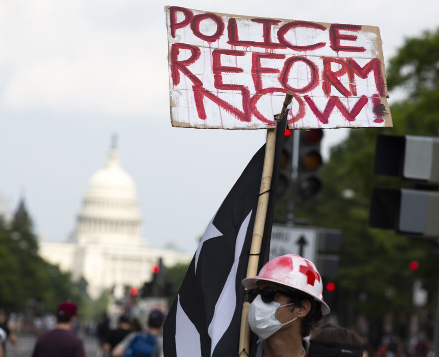 A demonstrator holds a placard during a march against racism and police brutality in Washington, D.C., on Saturday. Congressional Democrats have released a wide-ranging proposal aimed at overhauling policing