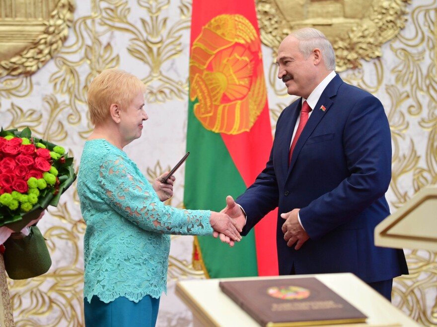Lidia Yermoshina (left) chairperson of the Belarusian Central Election Commission, hands over a presidential ID to President Alexander Lukashenko during an inauguration ceremony Wednesday at Independence Palace in Minsk.