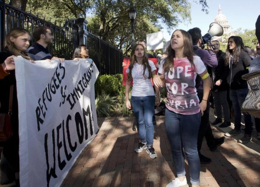 Demonstrators protest the state's actions toward blocking Syrian refugees from resettling in Texas.