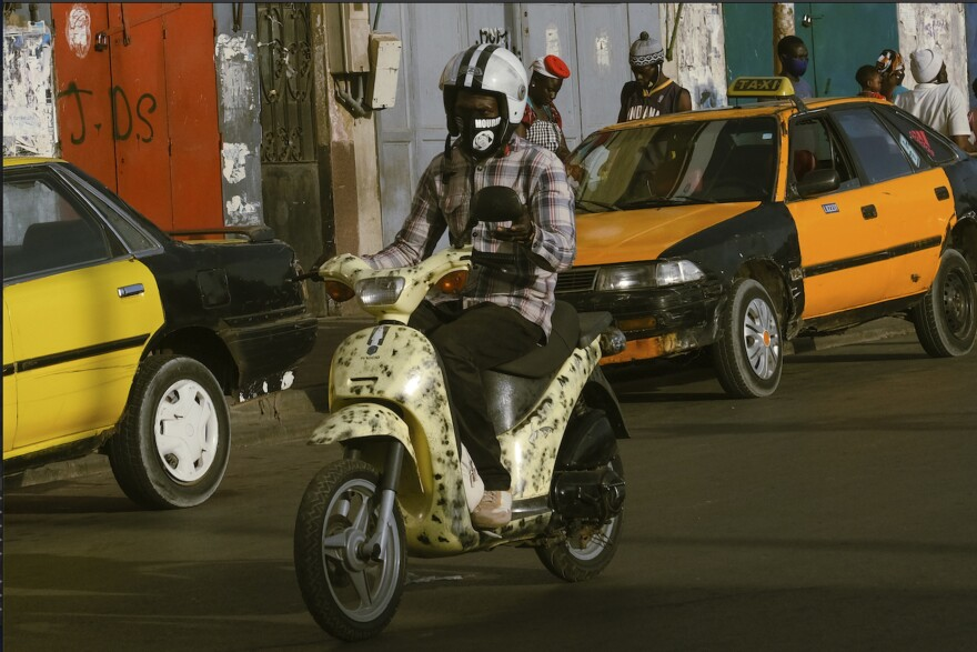 A motorbike rider in Dakar wears a mask with the silhouette of a local religious leader.