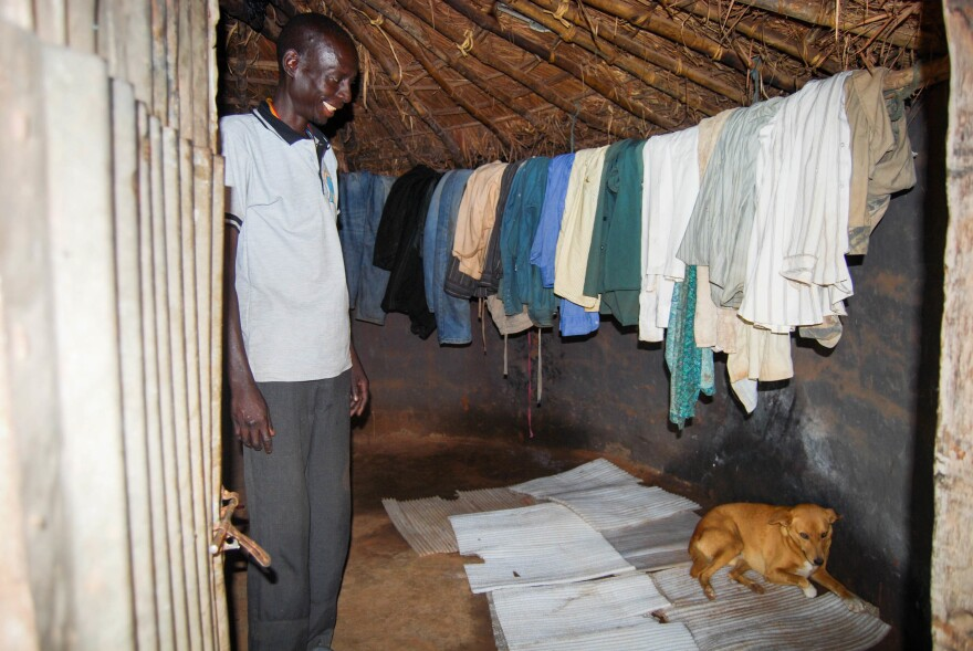 Charles Watmon and his dog, Ogen Rwot, in the house they share in Gulu, Uganda.