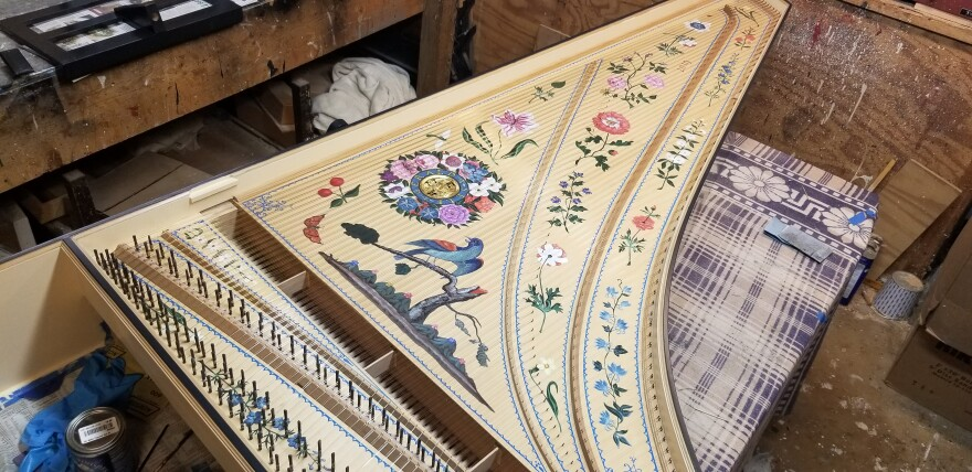 Paintings of flowers and birds populate the inside of this harpsichord case.