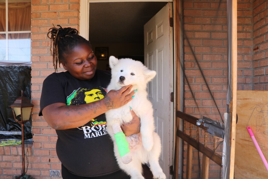 Chiquita Hodges holds a fluffy white puppy in her arms in front of a house she has been renting.