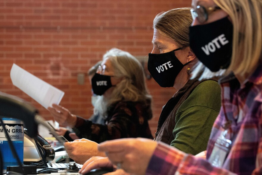 Poll workers wear face masks while preparing ballots at the Nederland Community Center in Nederland, Colo. on Nov. 3.