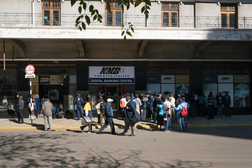People line up to use an ATM at NMB bank in Harare.