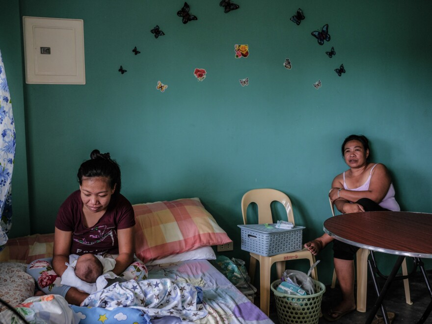 Mylene Madawat, 24, holds her newborn son. Her mother, Minda, right, is by her side. Because Madawat does not live near a health-care facility and home births are against the law in the Philippines, she rented an apartment in a community that has a hospital where she could give birth.
