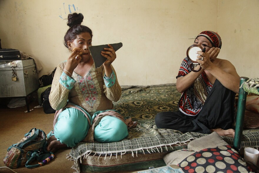 Shazia (left) and Nargis apply makeup before begging at a intersection in Lahore.