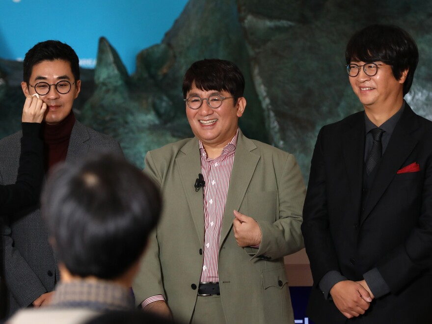 Chairman and CEO Bang Si-hyuk, center, photographed Oct. 15, 2020, the day his company, Big Hit Entertainment, debuted on the Korea Exchange in Seoul. To his left, Jiwon Park, Big Hit CEO of HQ & Management; right, Lenzo Yoon Big CEO of Global & Business.
