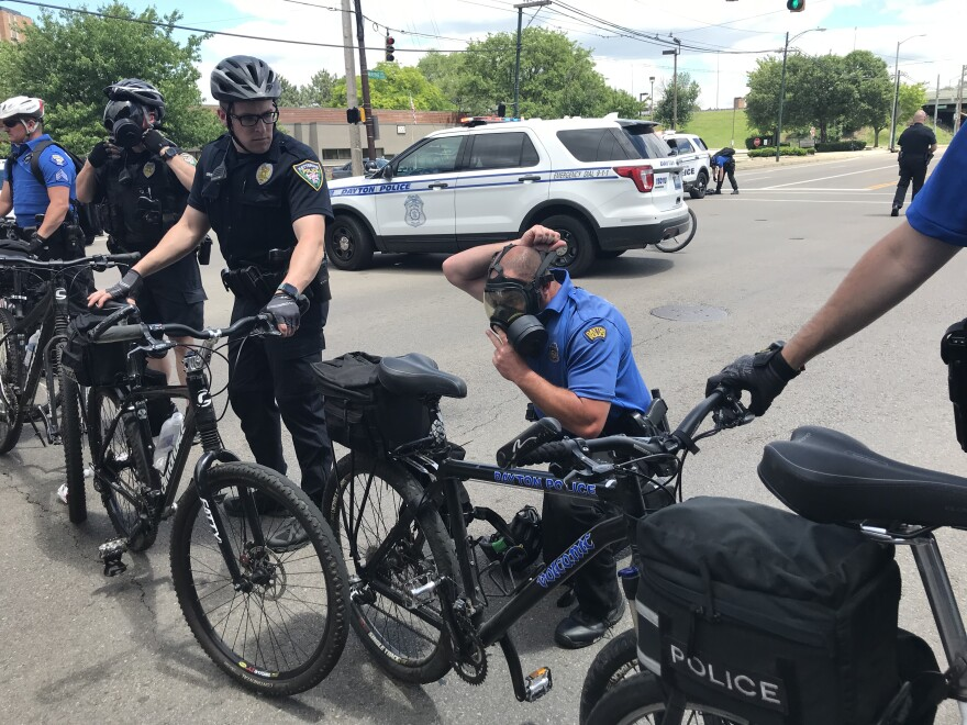 Police officers put on gas masks near the entrance of U.S. 35 on May 30 before using tear gas and pepper balls on the crowd.