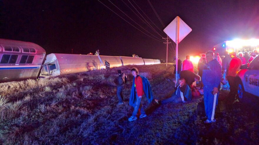 Passengers gather after their Amtrak train derailed near Dodge City, Kan., early Monday morning.