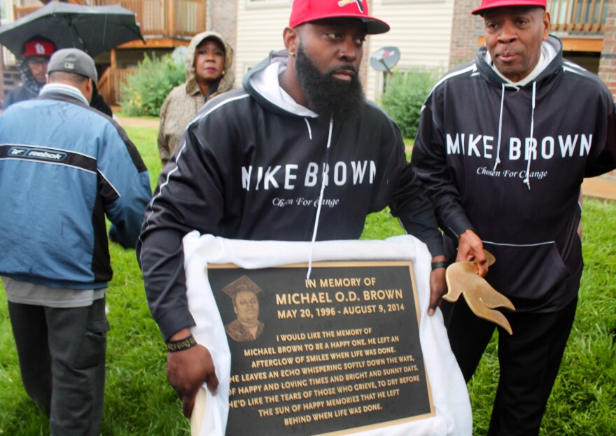 Michael Brown Sr., holds a plaque commemorating his son earlier this year.