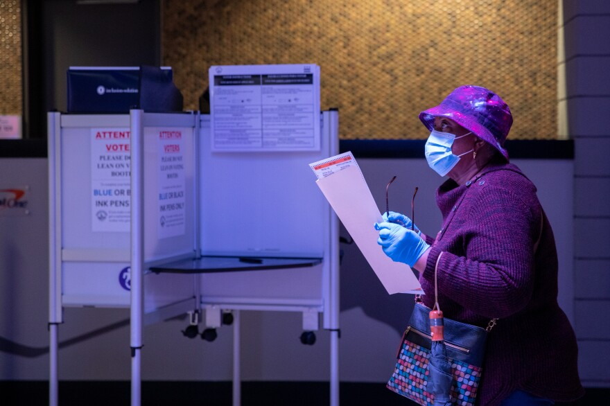 A woman stands in line with her ballot in order to have it scanned and counted on the first day of early voting at Capital One Arena in Washington, D.C., U.S., on Tuesday, October 27, 2020.