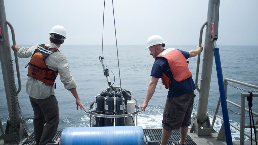 UC Santa Barbara's Jay Lunden and Andrew Brinkman, a summer intern for NOAA, prepare to deploy an instrument that measures temperature and salinity throughout the water column, and collects water samples.