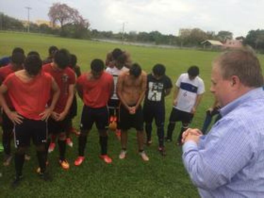 Silver Lake College was founded by Franciscan nuns in 1885. Here, the school's president, Chris Domes, offers a blessing to players trying out for Silver Lake's soccer Team