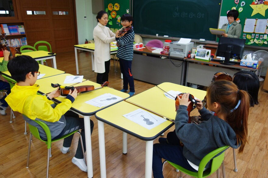 """A violin lesson at Ansan West Elementary School, where students come from so many different countries that the school has a """"multicultural coordinator"""" and language support for non-native Korean speakers."""