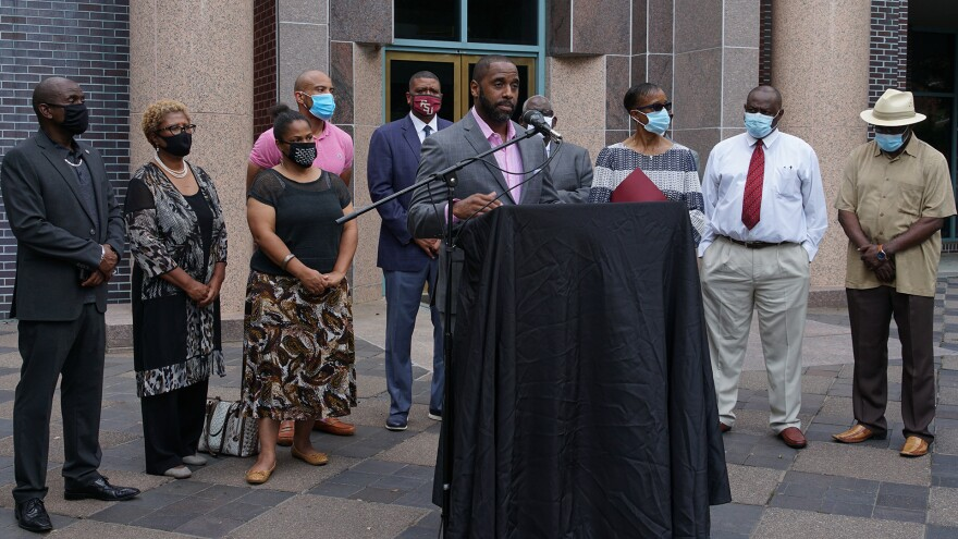 Nick Maddox stands at a podium draped in black cloth. A microphone is pointed at his mouth. He looks toward the press as he speaks. Behind him is City Hall and nine other people including City Commissioner Elaine Bryant.