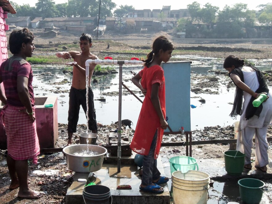 Slum dwellers near Calcutta get their water from a municipal pipe. Water coming out of the tap on the left is for bathing and so is untreated. The blue Zimba chlorinator is hooked up to the tap on the right, which is used for drinking water.