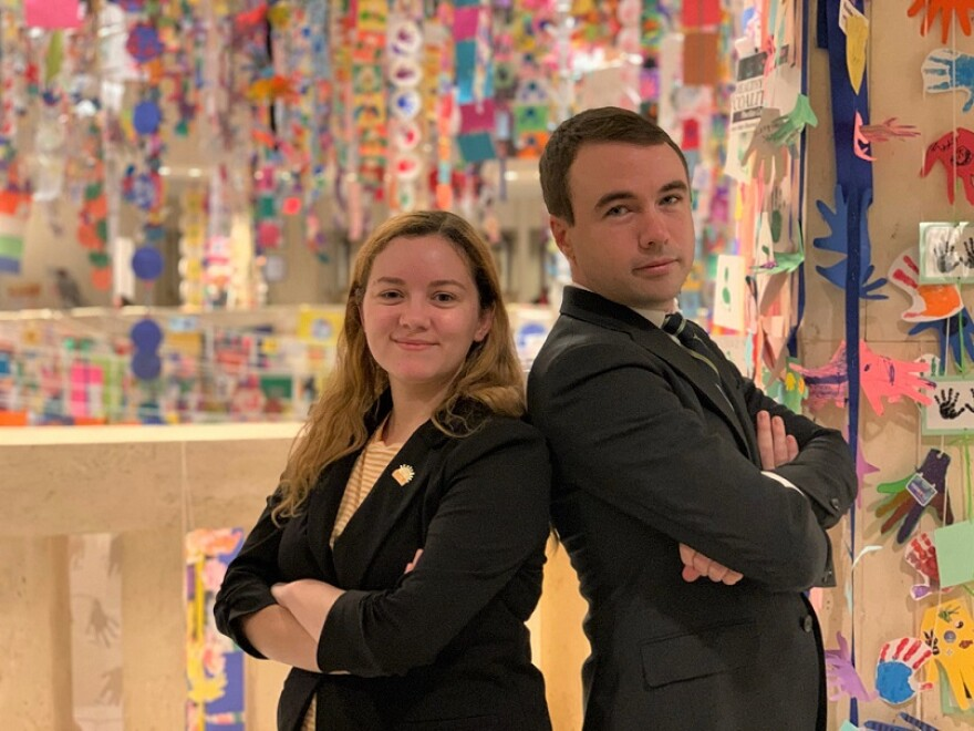 Rebekka Behr and Robert Latham stand back to back with their arms crossed inside the Capitol. The space behind them has colorful decorations for Children's Week.