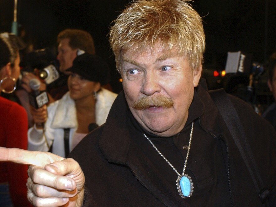 Rip Taylor talks with reporters before a film premiere in the Hollywood section of Los Angeles, in 2002. Taylor, the mustachioed comedian with a fondness for confetti-throwing who became a television game show mainstay in the 1970s, died Sunday.