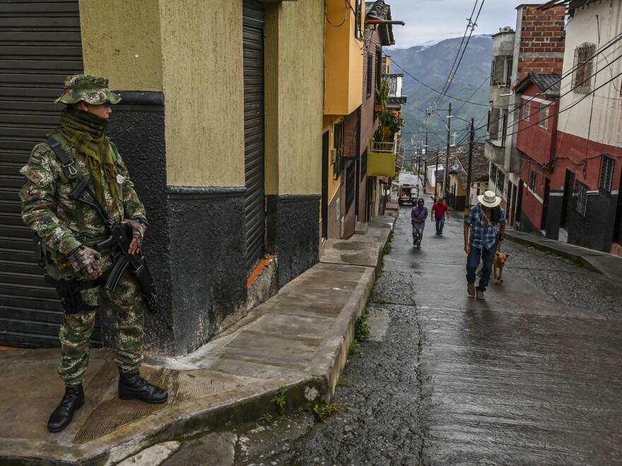 A soldier stands guard on a street in Ituango, Colombia, on Oct. 19, 2019. The town is home to a new public radio station staffed by ex-FARC rebels and war victims. Reporters often conduct interviews with former combatants and update listeners on the progress and setbacks of Colombia's peace accords.