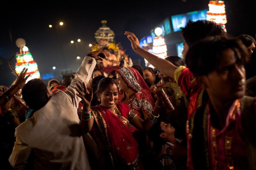 Wedding guests dance at a New Delhi celebration.