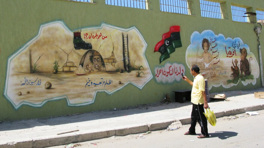 """A man takes a photo of an anti-Gadhafi mural in the Souk al-Joumah neighborhood of Tripoli, the Libyan capital. The former Libyan dictator often denounced the rebels who opposed him as """"rats."""" Now, young artists delight in painting pictures depicting the missing Gadhafi as a rat in a hole. This mural shows Gadhafi as a rat, with his son Saif."""