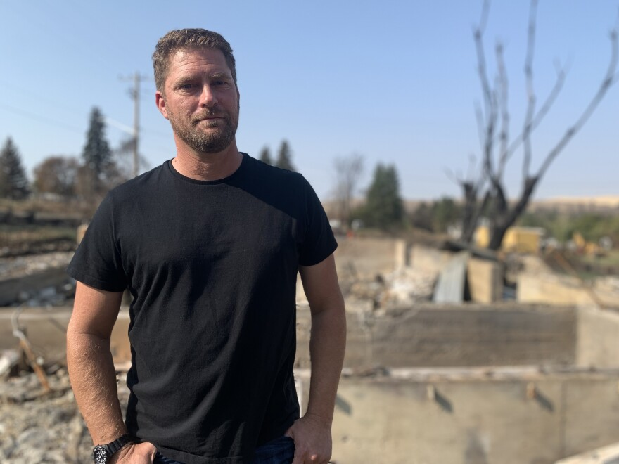 Scott Hokonson, a town council member and volunteer firefighter, stands in the rubble of his home, which was destroyed by the wildfire.