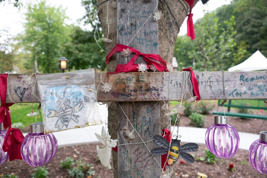 """A memorial for Belinda """"Bee"""" Scott at the tree where she was thrown from her house when the rapid flooding caused a gas explosion. She did not survive, and the surrounding land has been turned into a town park."""