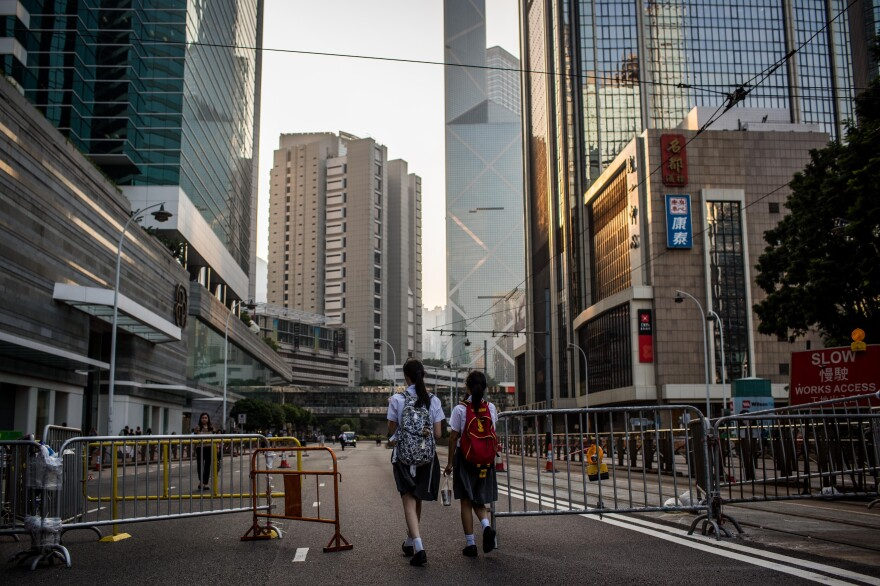 Two schoolgirls walk past a barricade on a street outside Hong Kong's government complex on Tuesday. Many protesters have returned to work and to school. Student leaders and government officials agreed Tuesday to hold talks on ending the protests.
