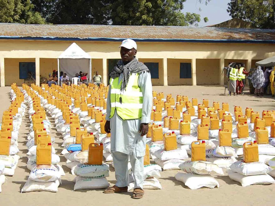 An official stands in front of relief materials at a camp for displaced people in Maiduguri in Borno State last week. The town, where many have gathered after fleeing Boko Haram attacks, is now said to be under assault from the Islamist extremist group.