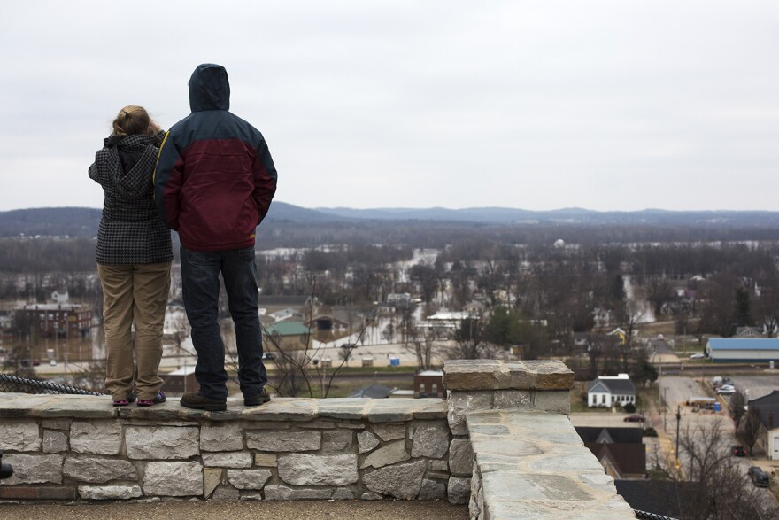 Residents stand atop a bluff at Blackburn Park in Pacific, Missouri Wednesday afternoon to take in the damage to their town.
