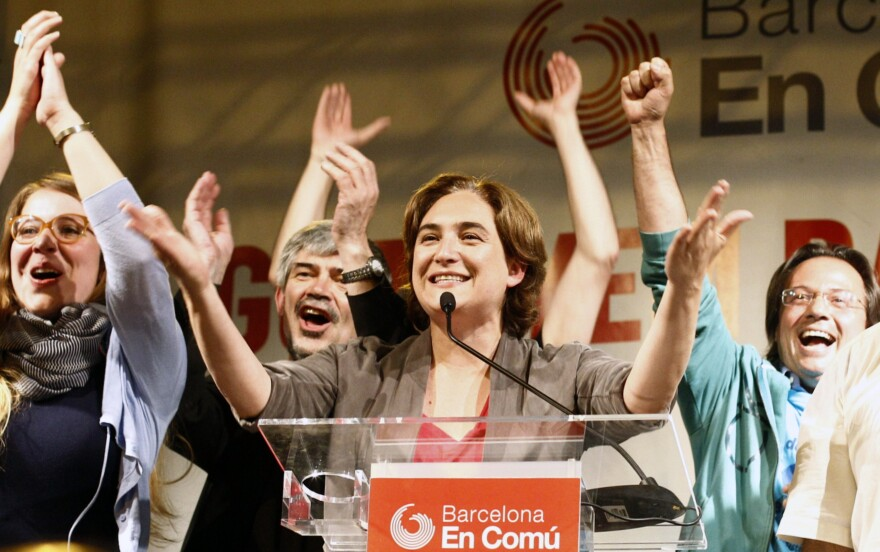 Ada Colau (center), leader of the Barcelona en Comú party, celebrates in Barcelona during a press conference following the results in Spain's municipal and regional elections on May 24. She is the first member of Spain's <em>indignados</em> protest movement to win public office.
