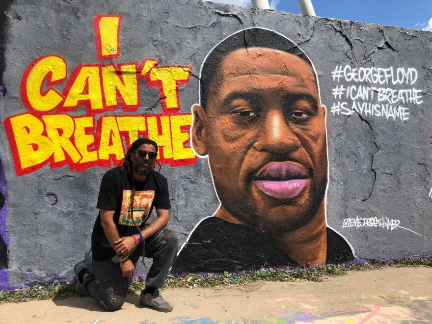 """Graffiti artist Eme Freethinker kneels in front of his portrait of George Floyd, which he painted on one of the last remaining sections of the Berlin Wall. """"I remember when I came in [to paint it], some guy told me, 'You have to do it with the police over his neck,'"""" Freethinker says, """"and I was like: 'No, man. Not like that. No.'"""""""