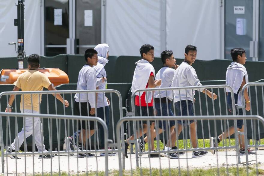 Migrant children are escorted through the Homestead Temporary Shelter for Unaccompanied Children on Good Friday, April 19, 2019.
