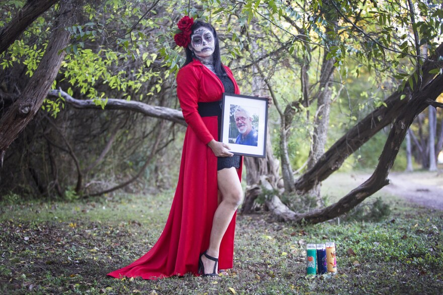 A woman dressed as a catrina poses in the park with a framed photograph of a friend who died.