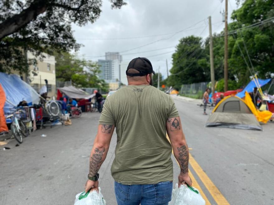 Man with bags of food walks through a homeless encampment in South Florida.